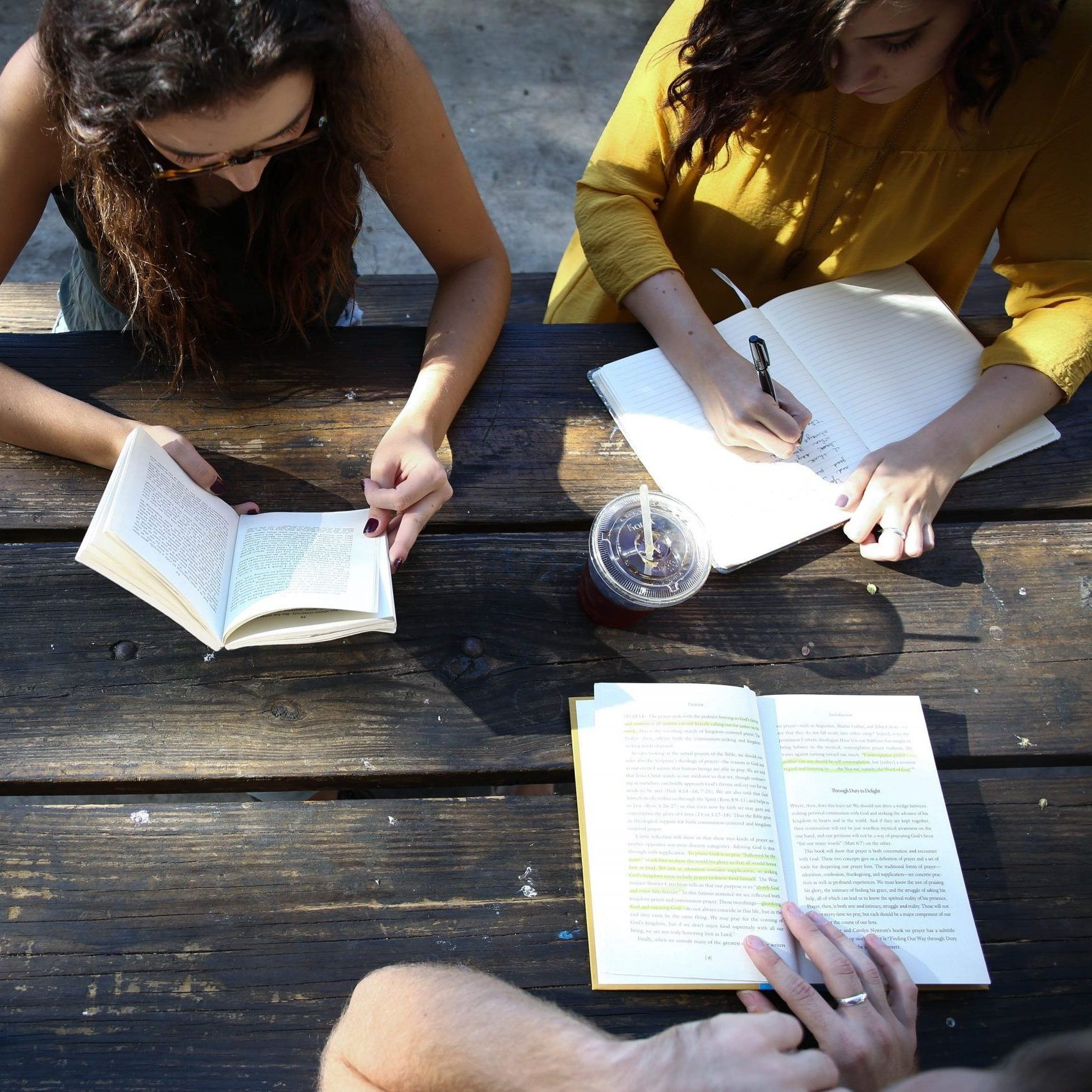Two girls sitting at a picnic table writing in journals.